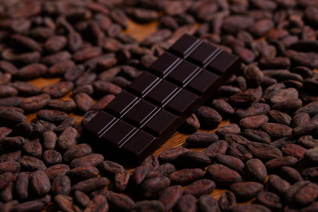 Tabulka čokolády ležící v kakaových bobech