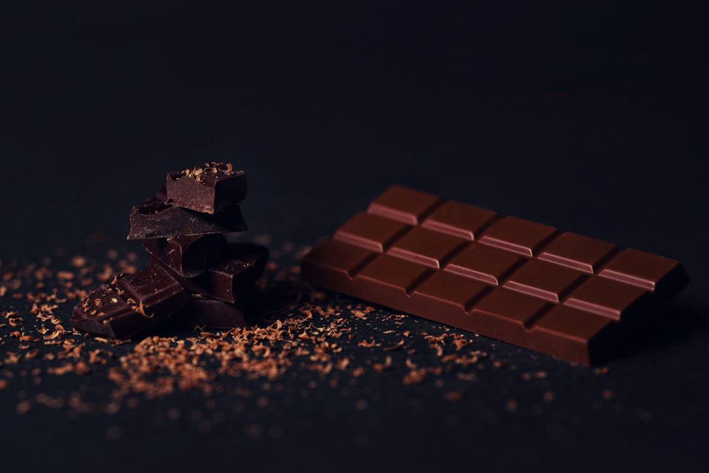 Tabulka čokolády a úlomky posypané čokoládovými hoblinami